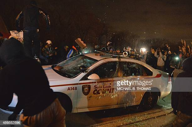 A police car is destroyed by protesters as demonstrators protest the death of 18yearold unarmed black teenager Michael Brown who was shot to death by...