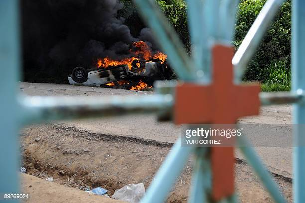 A police car is on fire outside the cemetery after an angry crowd detected two police officers during the funeral of Pedro Magdiel Munoz a supporter...