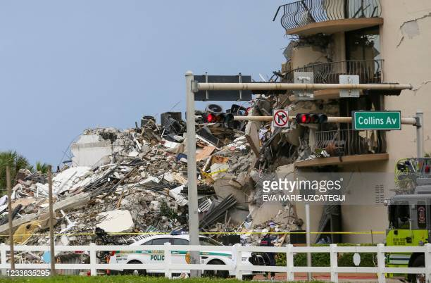 Police car is parked in front of debris from a partially collapsed building in Surfside north of Miami Beach, on June 24, 2021. - A high-rise...