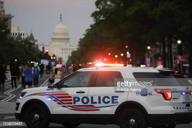 Police car is seen as hundreds of demonstrators rally hours after the arrest of a white police officer involved in the death of a black man George...