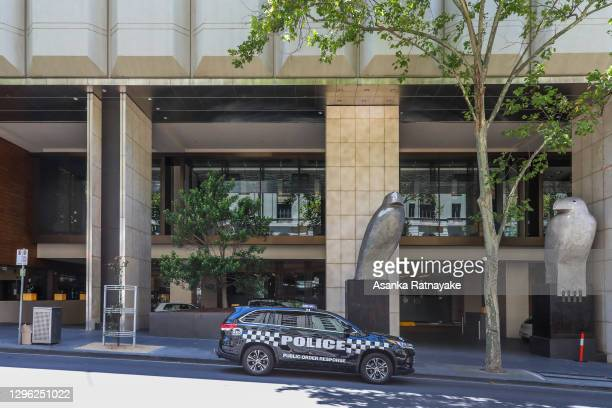 Police car is seen at the entrance of the Grand Hyatt hotel which is one of the three hotels being used for quarantine of players and accompanying...