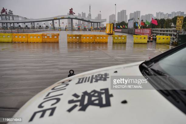 A police car is seen in front of one of the roads blocked by the police to restrict people leaving Wuhan in China's central Hubei province on January...
