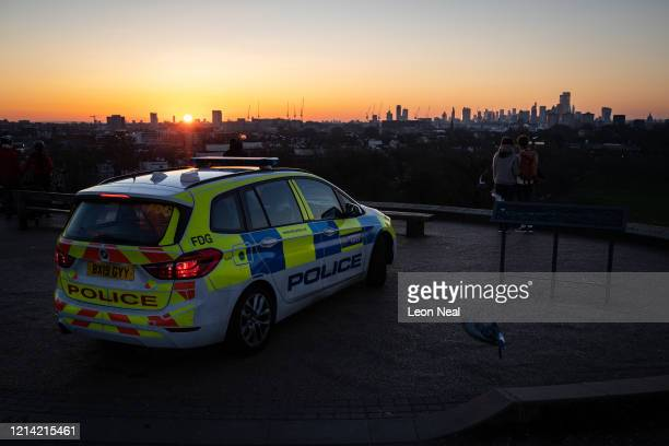 A police car is seen on Primrose Hill as the sun rises over the city on March 23 2020 in London United Kingdom The coronavirus pandemic has spread to...