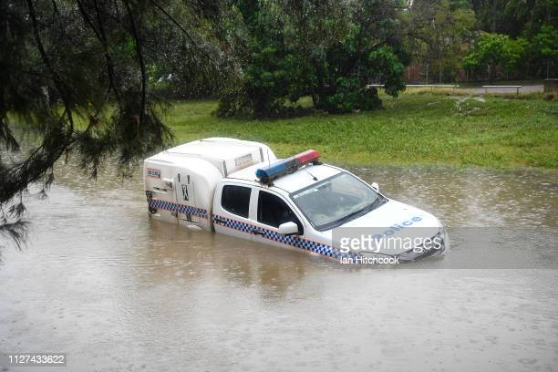 A police car is seen partially submerged in a drain after being swamped by flood waters on February 05 2019 in Townsville Australia Queensland...
