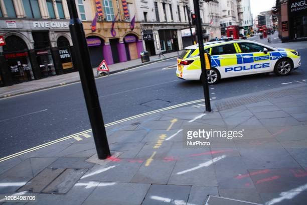 Police car on an emergency call races through Piccadilly Circus onto Haymarket in London, England, on March 28, 2020. The UK today began its first...