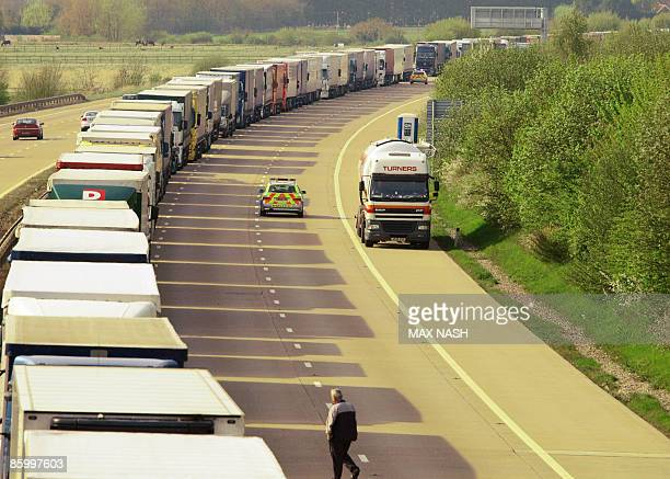 A police car passes a lorry driver walking towards his lorry in a long line of parked vehicles on the M20 motorway near Ashford Kent in southern...