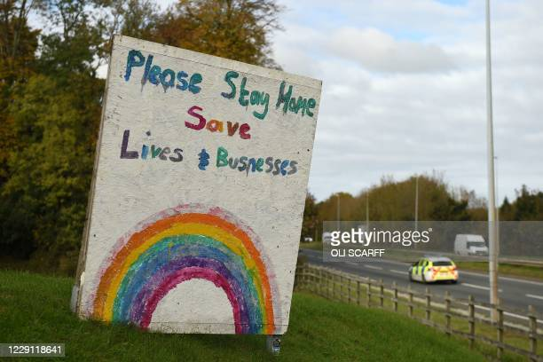 """Police car passes a sign asking people to """"stay home"""" outside a pub in Flint in north Wales on October 17 as further restrictions come into force as..."""