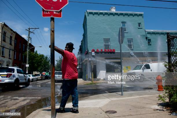 A police car passes as a man leans on a stop sign beside a spraying fire hydrant on July 20 2019 in Philadelphia PA With heat indexes reaching 105 to...