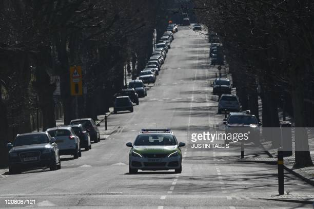 A police car patrols on a street in Tooting south London on March 24 2020 after Britain's government ordered a lockdown to slow the spread of the...