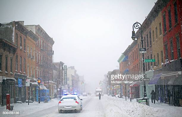 A police car patrols the in the snow on January 23 2016 in the Brooklyn borough of New York City The Northeast and parts of the South are...