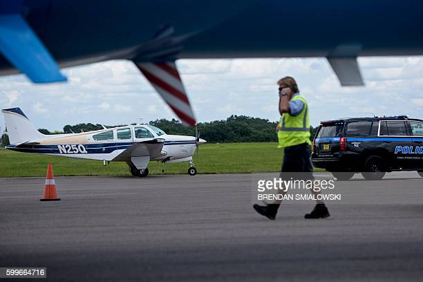 A police car pulls up along a small plane as it taxis past Democratic presidential nominee Hillary Clinton's plane at Tampa International Airport...