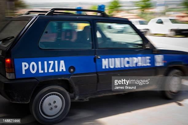 Police car speeds through town.
