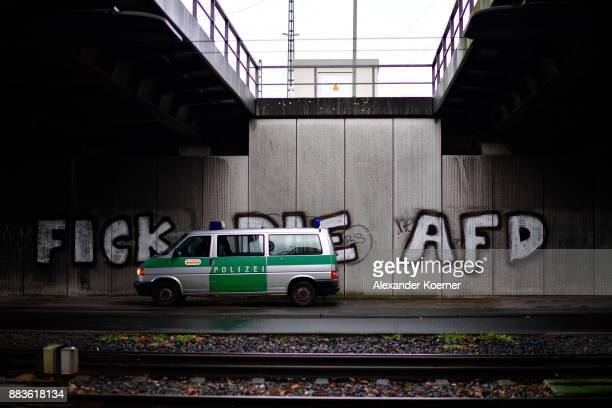 A police car stands in front of a slogan sprayed by leftwing protesters spells 'Fuck the AFD' close to the Hannover Congress Centrum on December 1...