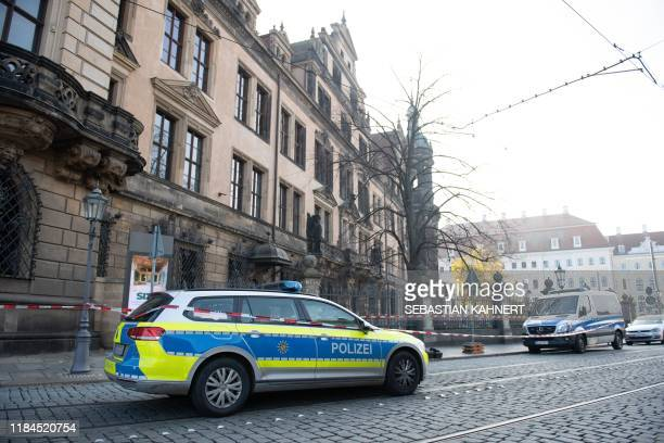 A police car stands in front of the cordoned off Royal Palace that houses the historic Green Vault in Dresden eastern Germany on November 25 after it...