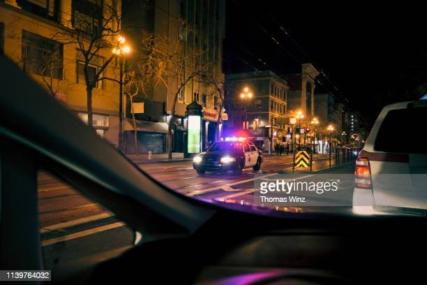 police car with emergency lights on in downtown district - police vehicle lighting stock pictures, royalty-free photos & images