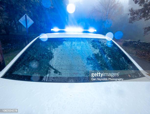 police car with flashing lights - police vehicle lighting stock pictures, royalty-free photos & images