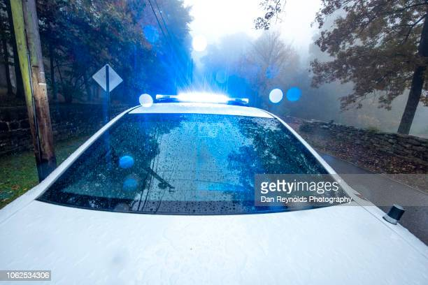 police car with flashing lights - police lights stock pictures, royalty-free photos & images