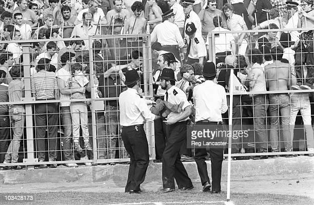 Police carry a terrified child from the overcrowded stands during an English second division match between Wimbledon and Manchester City held at...