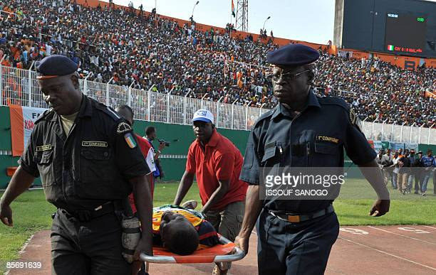 Police carry an injured person on March 29 2009 at Felix HouphouetBoigny stadium in Abidjan during the World Cup 2010 and African Cup of Nations...