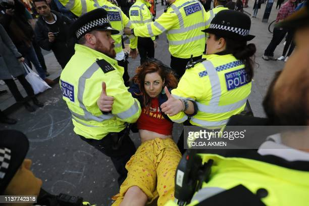 Police carry away a climate change activist protesting at Oxford Circus on the third day of an environmental protest by the Extinction Rebellion...