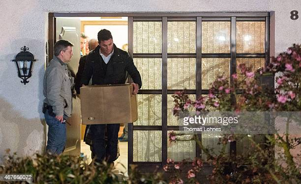 Police carry computer a box and bags out of the residence of the parents of Andreas Lubitz copilot on Germanwings flight 4U9525 on March 26 2015 in...