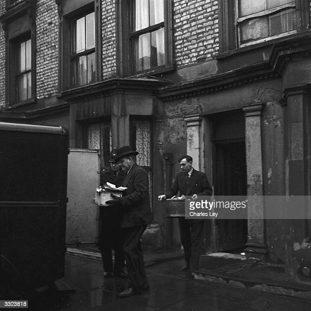 Police carry evidence from the scene of several murders 10 Rillington Place and the home of the murderer Reginald Christie