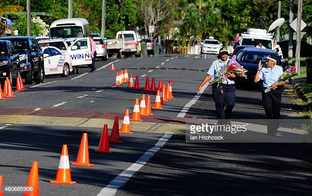 Police carry flowers to the scene of a multiple stabbing in the suburb of Manoora on December 19 2014 in Cairns Australia Eight children have been...