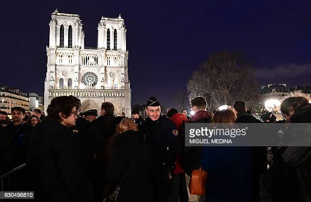 Police carry out searches on visitors as they access a security perimeter in front of the NotreDame Cathedral in central Paris on Christmas eve...