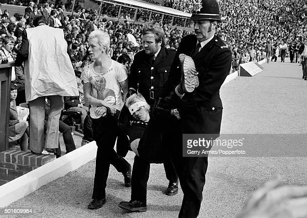 Police carrying a man out of the ground after violence during the First Division match between Birmingham City and Liverpool at St Andrews in...