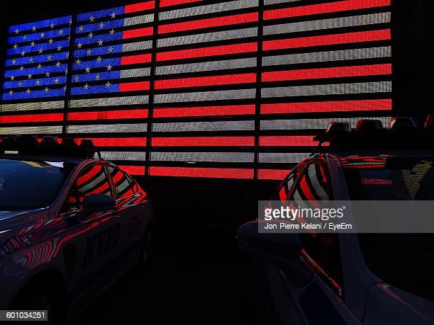 Police Cars Against Illuminated American Flag On Wall