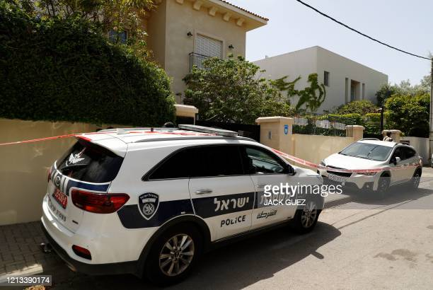Police cars and a red ribbon block the entrance to the residence of Israel's Chinese ambassador on the outskirts of Tel Aviv, after he was found dead...