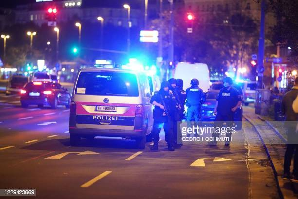 Police cars and armed police offficer stand in central Vienna on November 2 following a shooting near a synagogue. - Multiple gunshots were fired in...