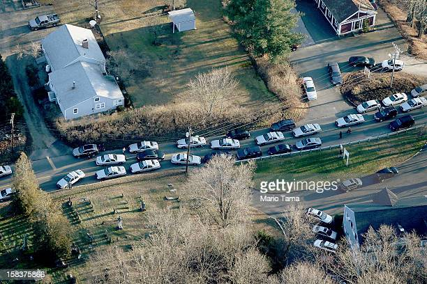 Police cars and other vehicles fill a road near the scene of a mass school shooting at Sandy Hook Elementary School on December 14 2012 in Newtown...