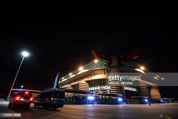 Police cars are parked in front of the San Siro stadium closed to the public as a safety measure against the COVID19 the novel coronavirus ahead of...