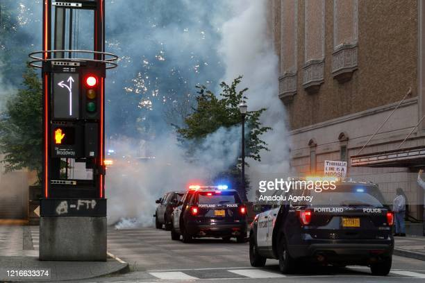 Police cars are seen as demonstrators are enveloped in tear-gas during a protest over the death of George Floyd an unarmed black man who died after...