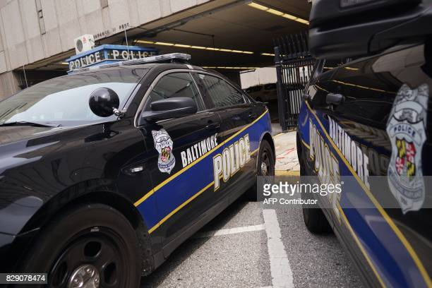 Police cars are seen outside of the Baltimore City Police Headquarters in Baltimore on August 8 2017 Baltimore a city of 28 million is troubled by...
