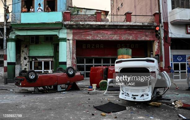 Police cars are seen overturned in the street in the framework of a demonstration against Cuban President Miguel Diaz-Canel in Havana, on July 11,...