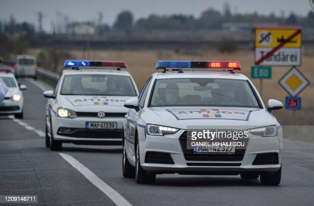 Police cars drive on a road at the entrance of the town of Tandarei, where a complete lockdown has been in place, due to the novel coronavirus...