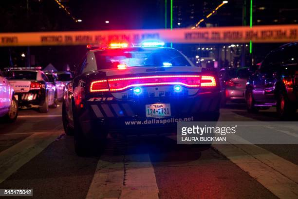 TOPSHOT Police cars sit on Main Street in Dallas following the sniper shooting during a protest on July 7 2016 A fourth police officer was killed and...