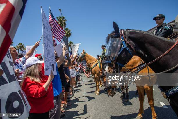 Police cavalry move protesters out of the street while they gather in a demonstration on May 01 2020 in Huntington Beach California The demonstration...