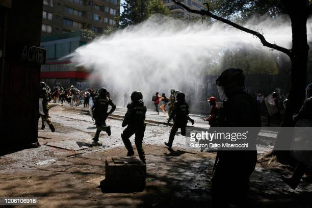 Police charge against protesters near the Plaza Italia at an International Women's Day celebration on March 8 2020 in Santiago Chile
