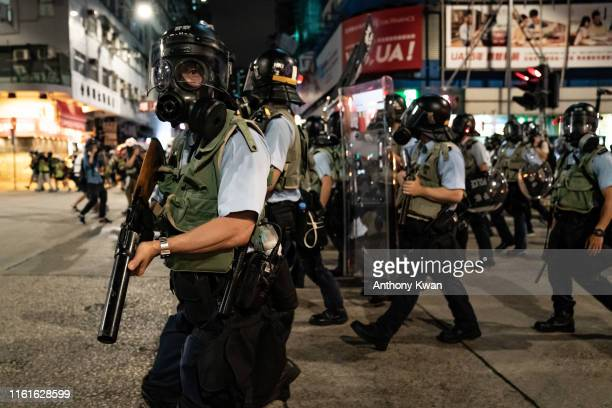 Police charge on a street during a demonstration on Hungry Ghost Festival day in Sham Shui Po district on August 14 2019 in Hong Kong China...