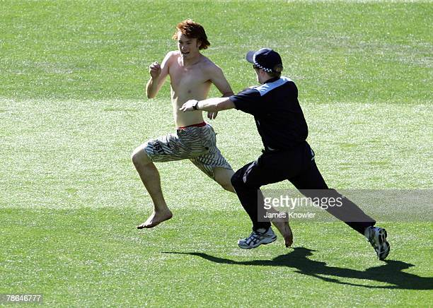Police chase a streaker during day one of the First Test match between Australia and India at the Melbourne Cricket Ground on December 26 2007 in...