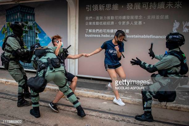 TOPSHOT Police chase down a couple wearing facemasks in the central district in Hong Kong on October 5 a day after the city's leader outlawed face...