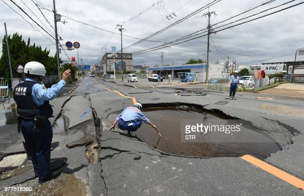 TOPSHOT Police check a collapsed road following an earthquake in Takatsuki north of Osaka prefecture on June 18 2018 At least two people including a...