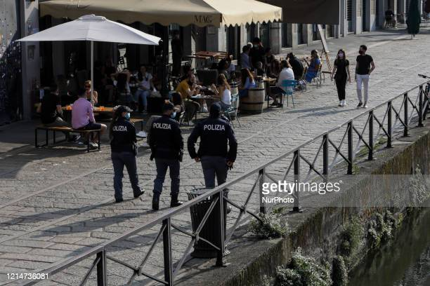 Police check Navigli at the beginning of the weekend in Milan on May 22 2020 in Milan Italy Restaurants bars cafes hairdressers and other shops have...