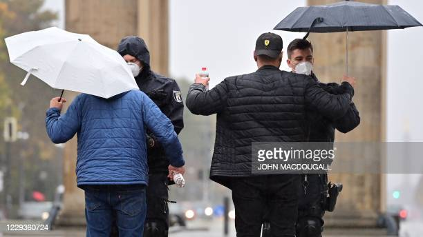 Police check participants ahead of a rally of Palestinian and Arab associations in front of the Brandenburg Gate and near the French embassy in...