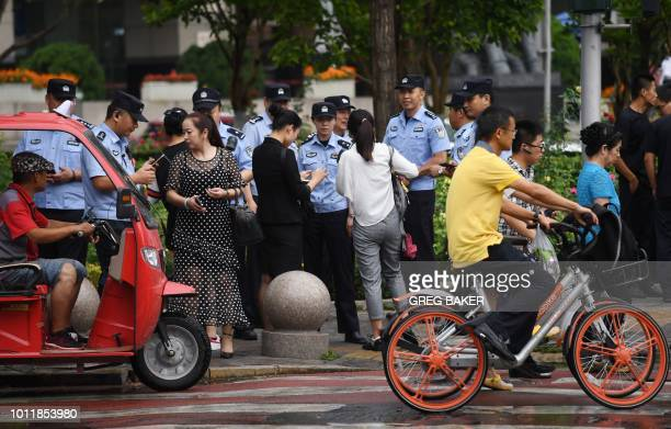 Police check the identification of passersby as they search for petitioners near China's Banking Regulatory Commission in Beijing on August 6 2018...