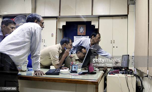 Police checking the CCTV footage during the investigation of bizarre bank robbery at Syndicate Bank's Sector 18 branch on July 2 2013 in Noida India...