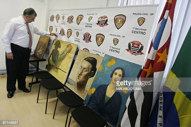 A police chief agent presents to the media recovered paintings Figura em Azul by Brazilian artist Tarsila do Amaral Retrato de Maria and Cangaceiro...